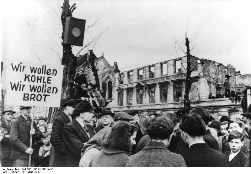 Foto: Bundesarchiv, Bild 183-B0527-0001-753 / CC-BY-SA 3.0, via Wikimedia Commons U.B.z.: Wegen der katastrophalen Ernährungslage legten am Montag, 31.3.1947, in Krefeld Tausende die Arbeit nieder und versammelten sich zu einer Protestkundgebung auf dem Karlsplatz. Zahlreiche Transparente brachten die Forderungen der Arbeiter zum Ausdruck.